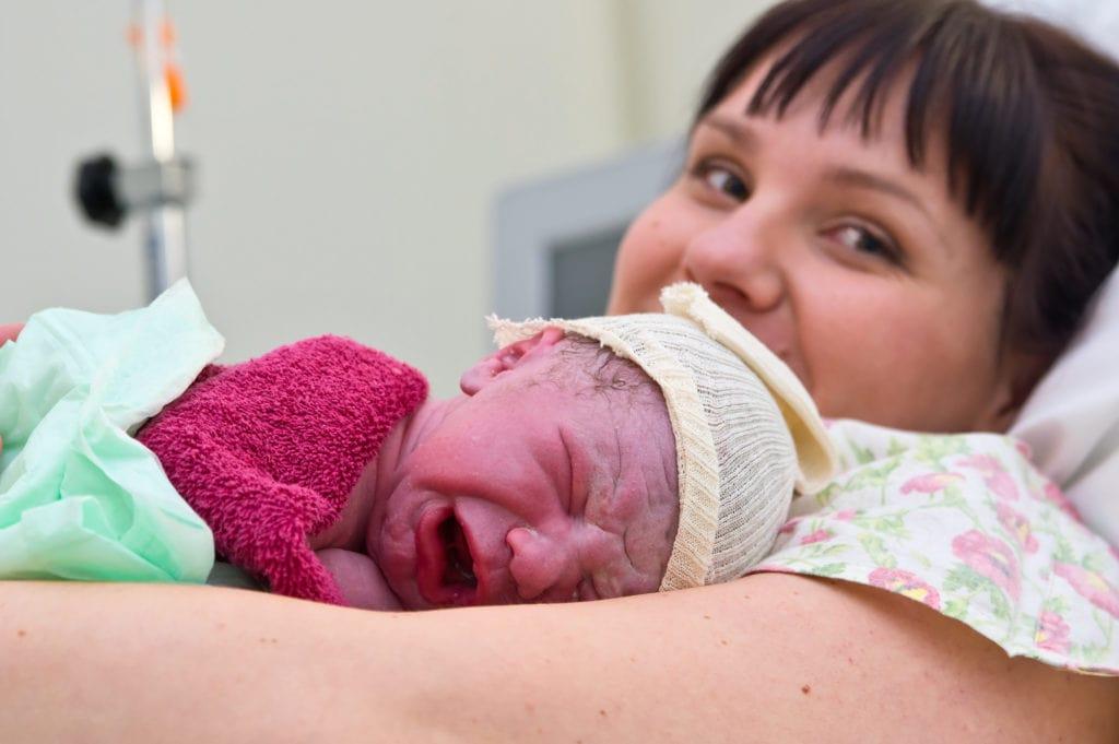 smiling mom with freshly born newborn